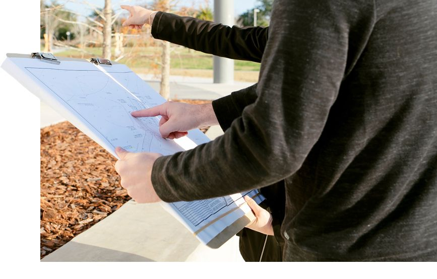 engineers pointing at a paper with plans while standing outside